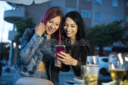 two friends sitting in bar using