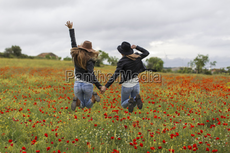two woman jumping poppy field holding