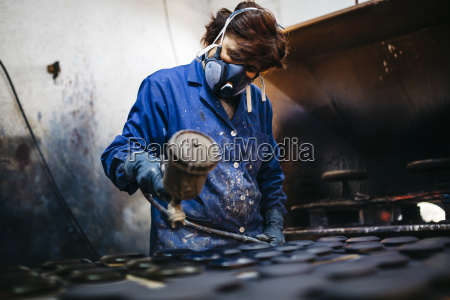 female worker painting ceramics with spray