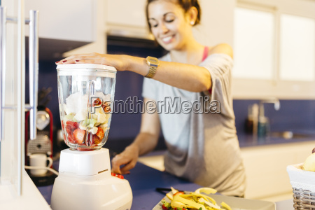young woman in kitchen preparing a