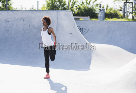 young woman stretching in skatepark