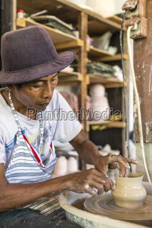 potter in workshop working on earthenware