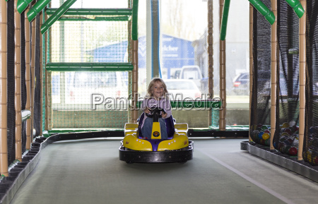 excited little girl driving bumper car
