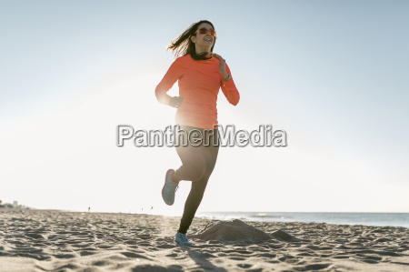 woman jogging on the beach early