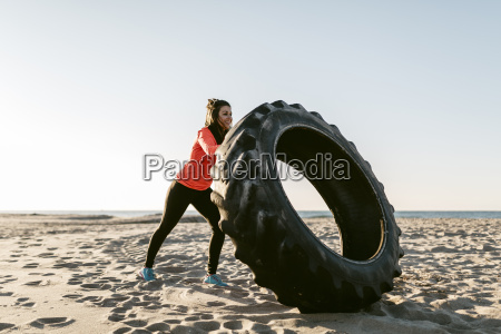 woman doing sports with tractor tire