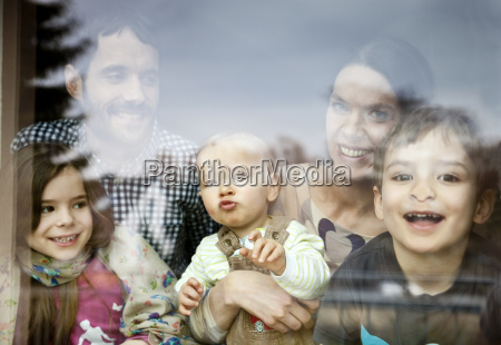 happy family of five looking through