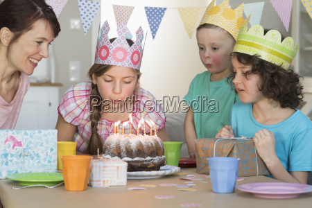 girl blowing out candles on birthday