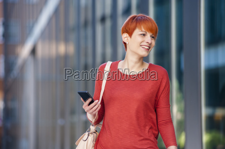smiling young woman holding cell phone