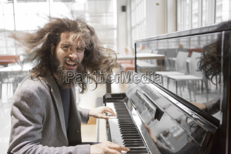 young hipster playing piano