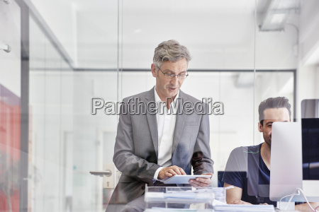 mature businessman in office using digital