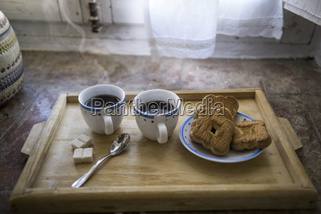wooden tray with two cups of
