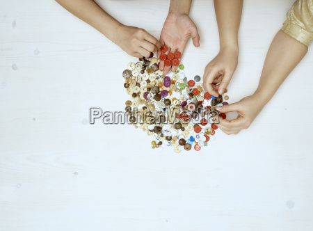 hands sorting buttons