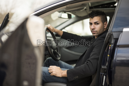 serious young man sitting in car