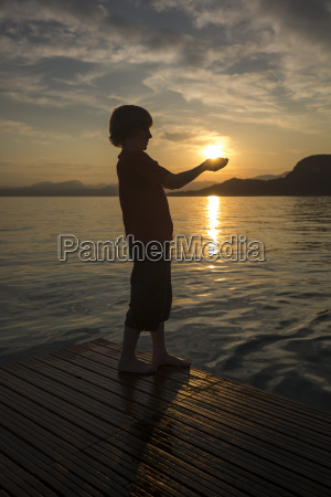 boy holding hands against the sun