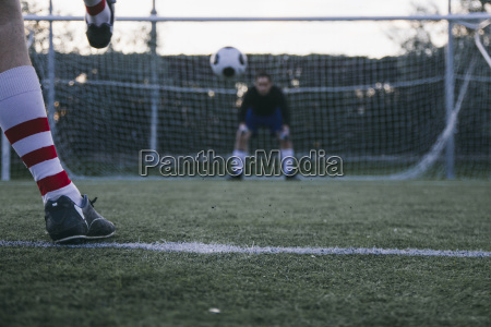 legs of a footnball player kicking
