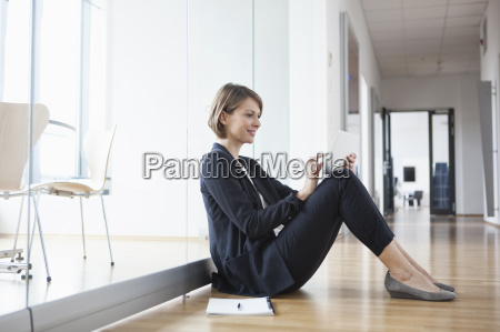 businesswoman sitting on office floor using