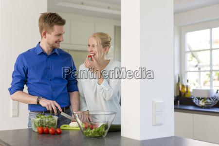 couple in kitchen preparing a salad