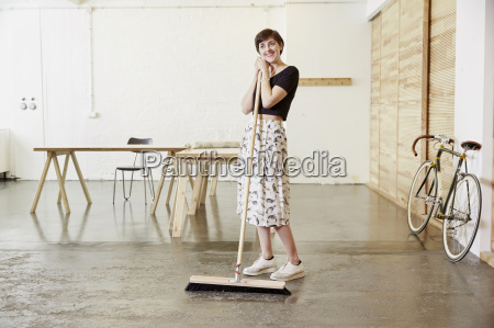 smiling woman with broom in a