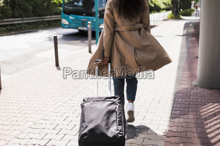 young woman with luggage at bus