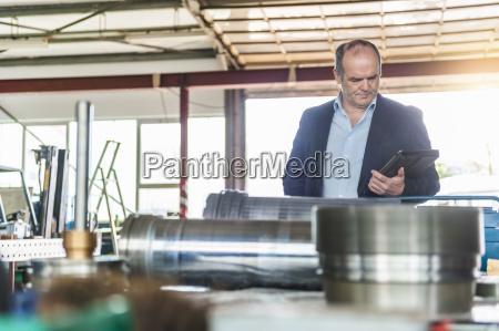 workshop senior man with digital tablet