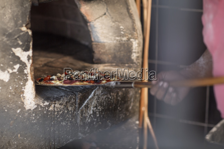 man putting pizza in pizza oven