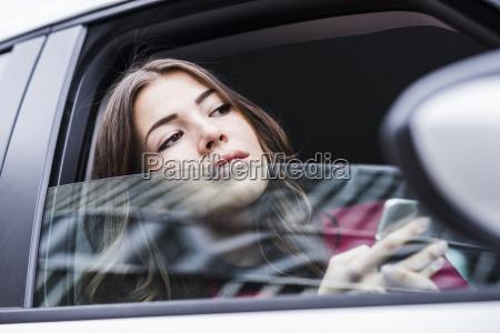 brunette woman sitting in car looking