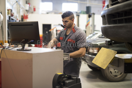mechanic looking on computer screen at