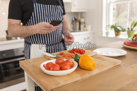 man using smartphone while preparing food