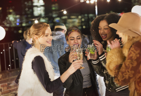 young women drinking and enjoying rooftop