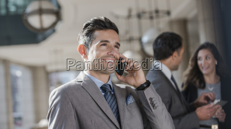 smiling corporate businessman talking on cell