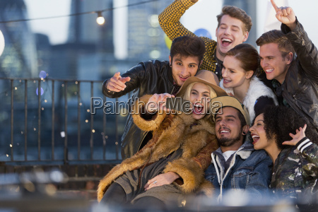 enthusiastic young adult friends taking selfie