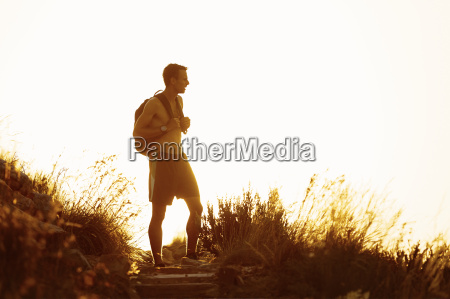bare chested male hiker with backpack