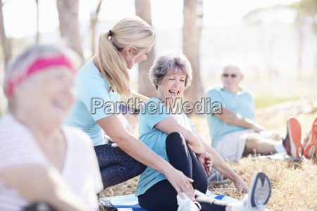 yoga instructor guiding senior woman in