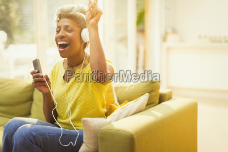 playful mature woman listening to headphones