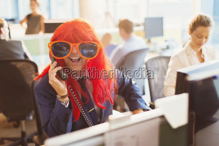 portrait playful businessman wearing red wig