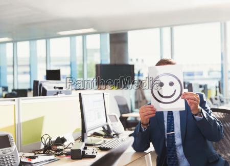 portrait of businessman holding smiley face