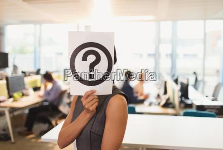 portrait of businesswoman holding question mark