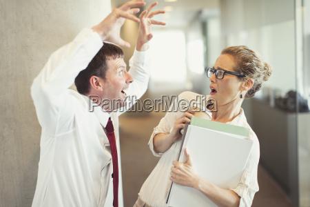 businessman making snarling gesture at terrified