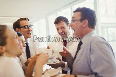 business people laughing and drinking coffee