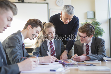 teacher guiding high school students studying