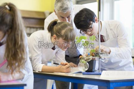teacher helping high school students conducting