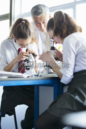 teacher helping high school students using