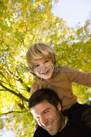 father carrying son on shoulders in