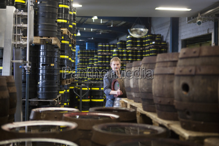 brewer with beer kegs at brewery