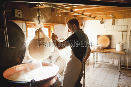 mid adult man making cheese in