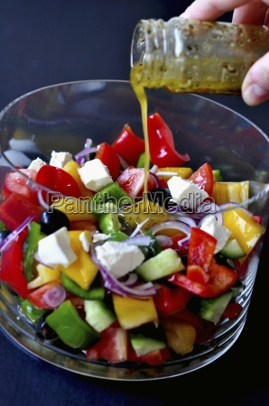 dressing being poured over a vegetable