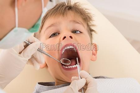 dentists hand examining teeth of child