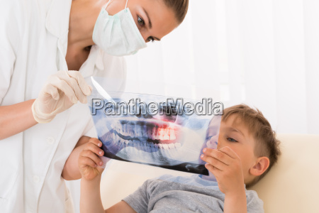 dentist showing teeth xray to child