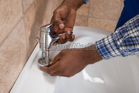 plumbers hand fixing tap of sink