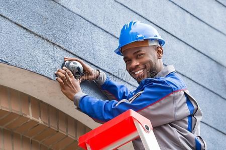 male technician repairing camera